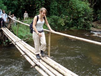 Crossing stream on Doi INthanon trek Thailand
