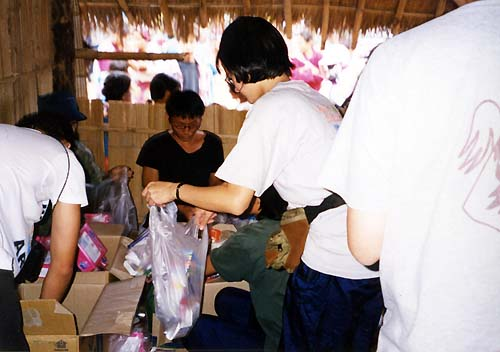 Helping giving supplies to needy villagers